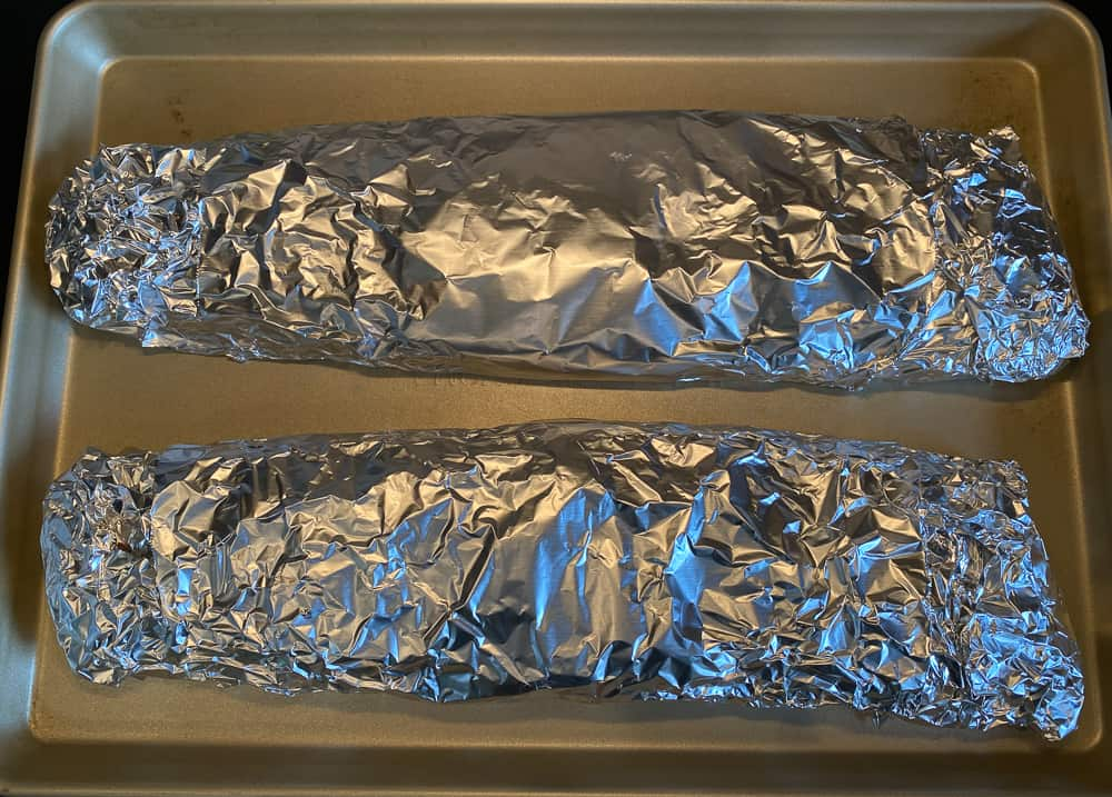 photo of ribs wrapped in foil on a baking pan