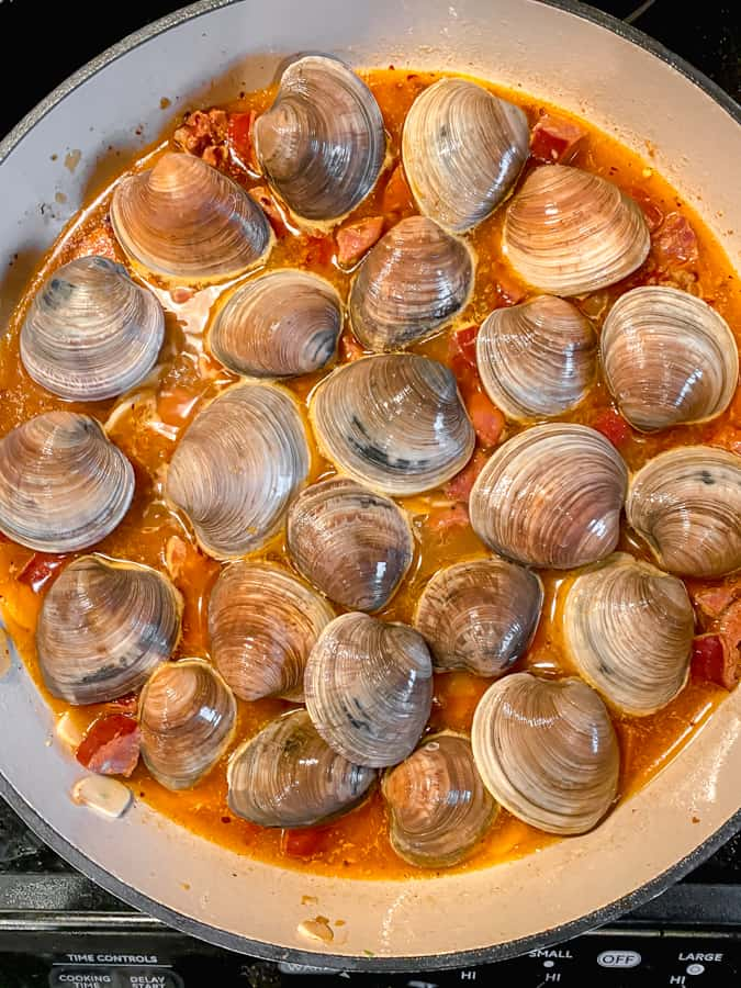 closed clams in chorizo broth prior to steaming open