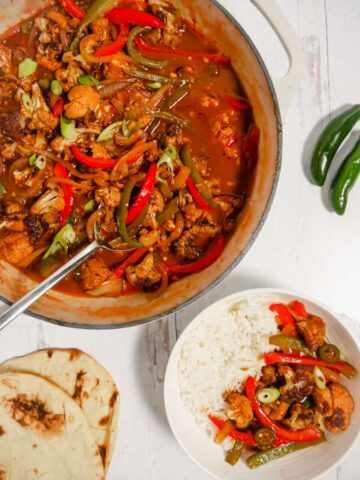 overhead photo of skillet with cauliflower and peppers, naan bread, and basmati rice in bowl