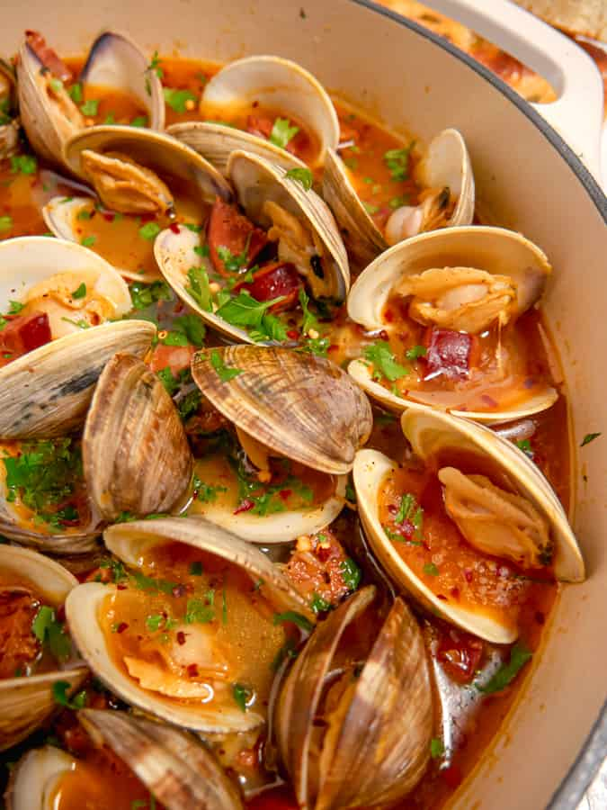 close up of steamed clams in chorizo broth