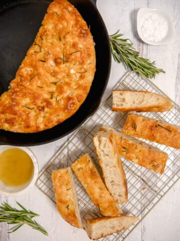overhead photo of focaccia bread in a cast iron skillet, sliced bread, olive oil and rosemary
