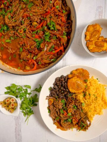 overhead photo of shredded beef in a pot with a plate of ropa vieja, yellow rice, black beans, and tostones