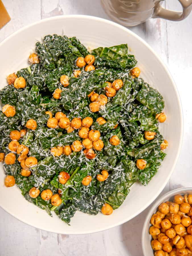 overhead photo of kale caesar salad topped with chickpeas and parm cheese with bowl of chickpeas to the side