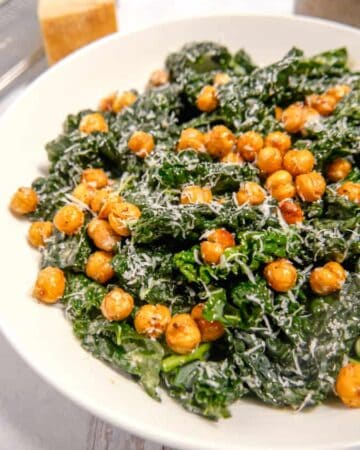 zoomed in photo of kale caesar salad in a bowl topped with parmesan and chickpeas