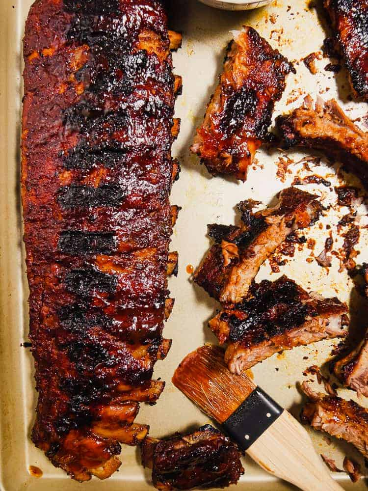 overhead shot of rack of bbq grilled ribbs and cut ribs on a platter with bbq brush