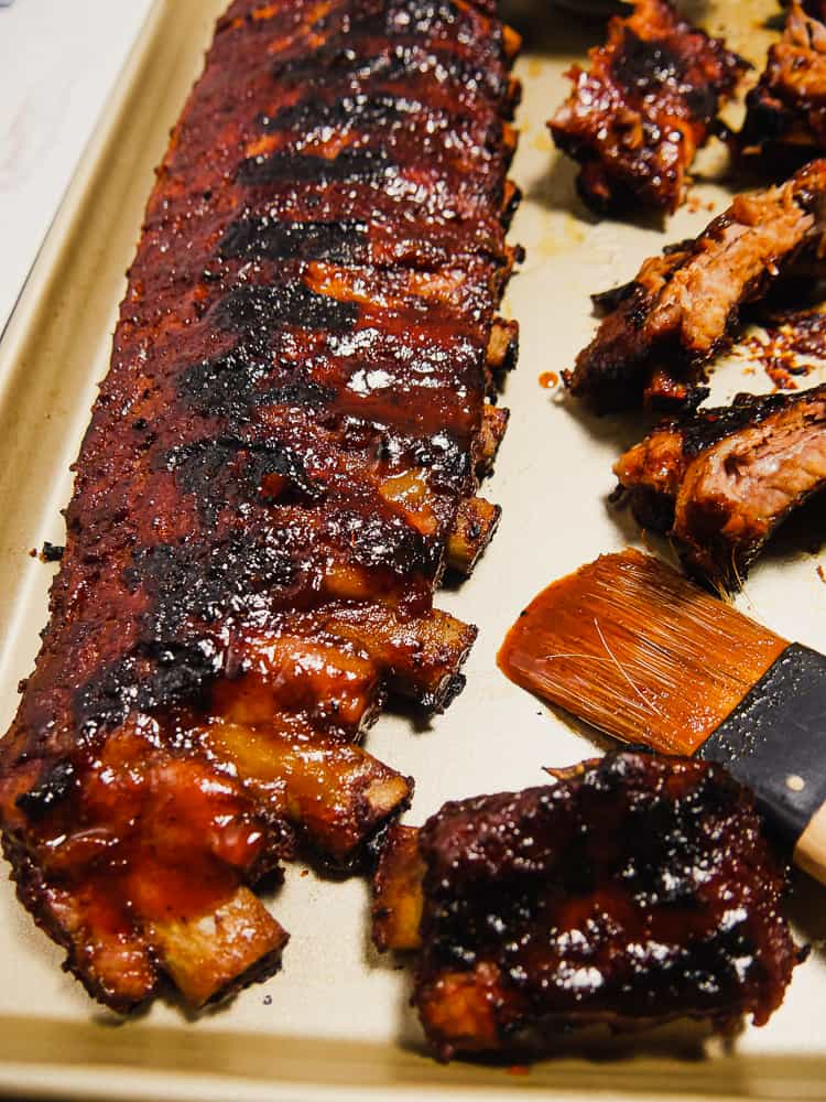 close up photo of rack of ribs covered in BBQ sauce on platter, with BBQ brush to the side