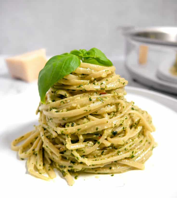 twirled spaghetti on a white plate tossed in pesto with basil leaves on top