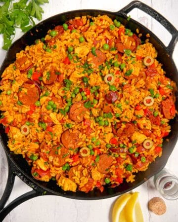 overhead photo of paella in a cast iron skillet with herbs and lemon surrounding