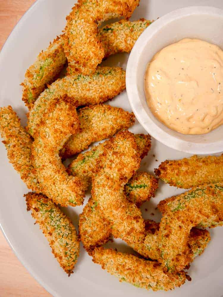 close up shot of panko breaded avocado fries on a plate with dipping sauce