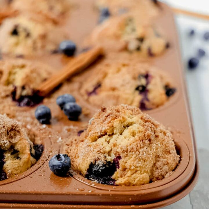 close up of copper muffin tin with blueberry muffins and loose fresh blueberries around