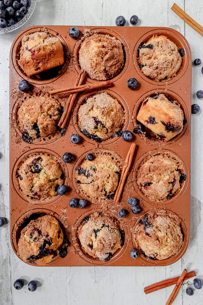 overhead photo of blueberry muffins in a muffin tin surrounded by fresh blueberries and cinnamon sticks