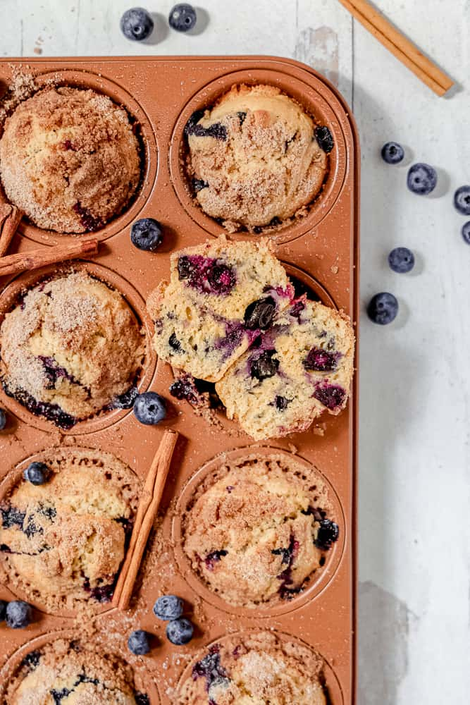 close up of blueberry muffin cut in half with blueberries showing