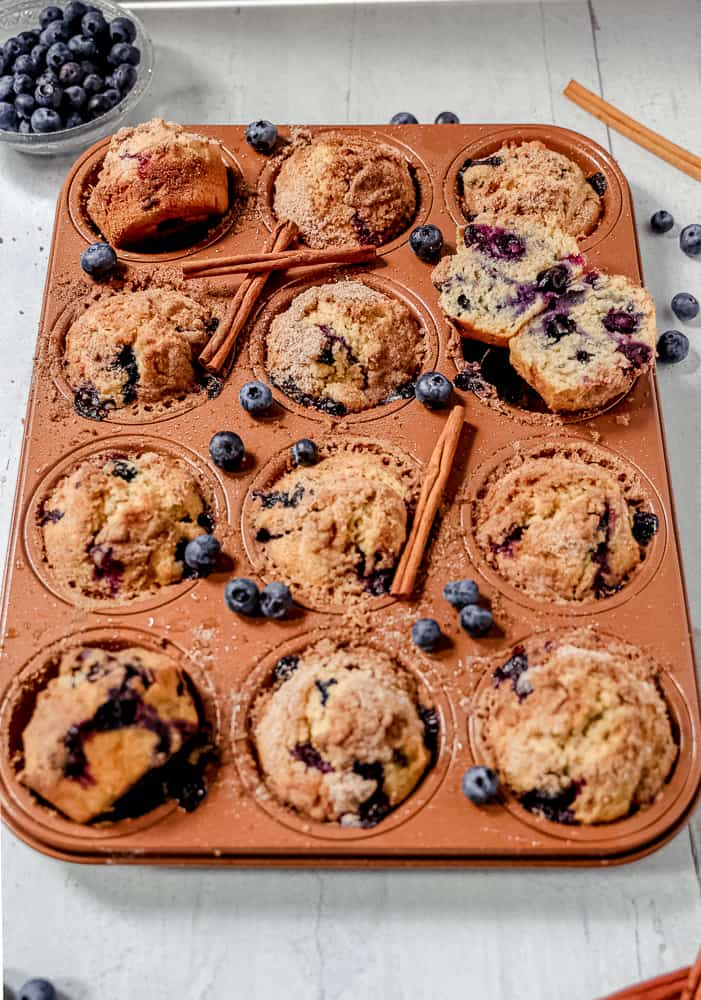 copper muffin tin with blueberry muffins inside each cup, loose blueberries and cinnamon sticks sprinkled around with cup of blueberries in background