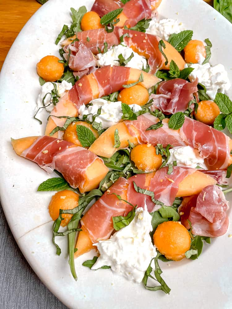 close up of melon wrapped in prosciutto on a plate with herbs and burrata cheese