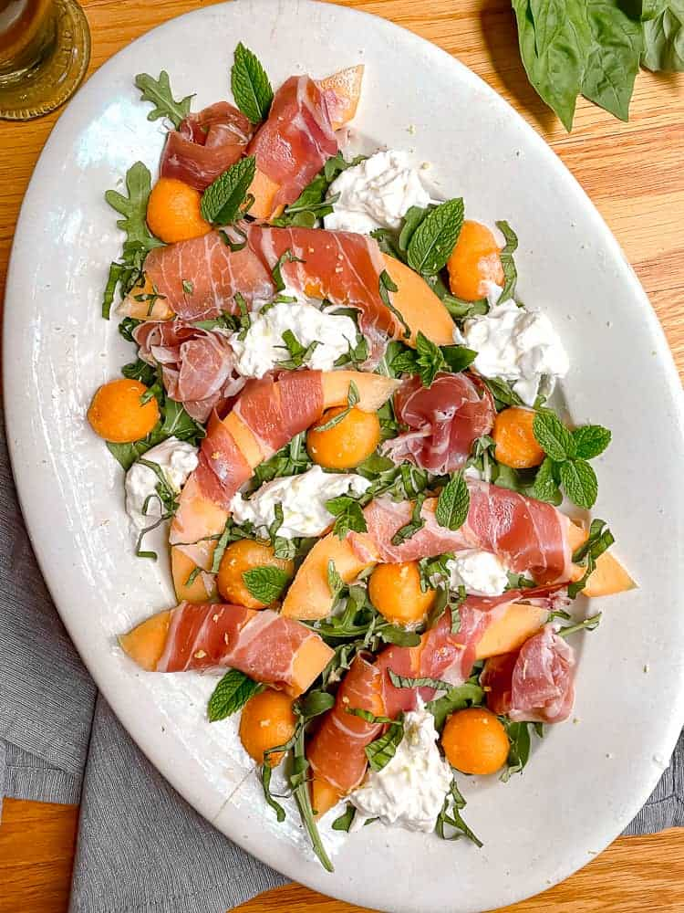 white serving dish with melon wrapped in prosciutto, fresh basil, mint, and burrata cheese