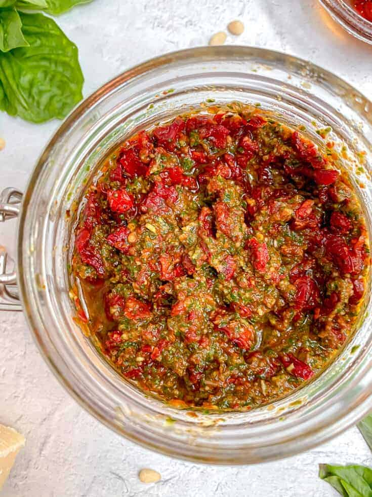 overhead photo of a glass jar filled with pesto and sun dried tomatoes, surrounded by fresh basil leaves and a cheese block