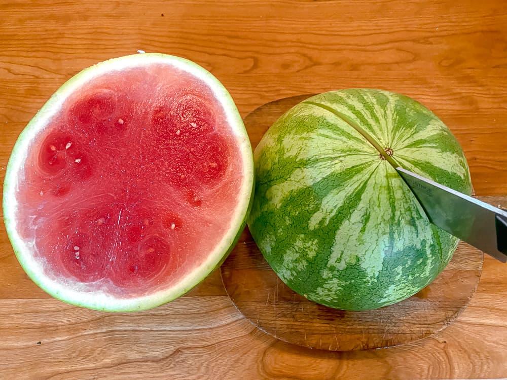 watermelon cut in half on a cutting board