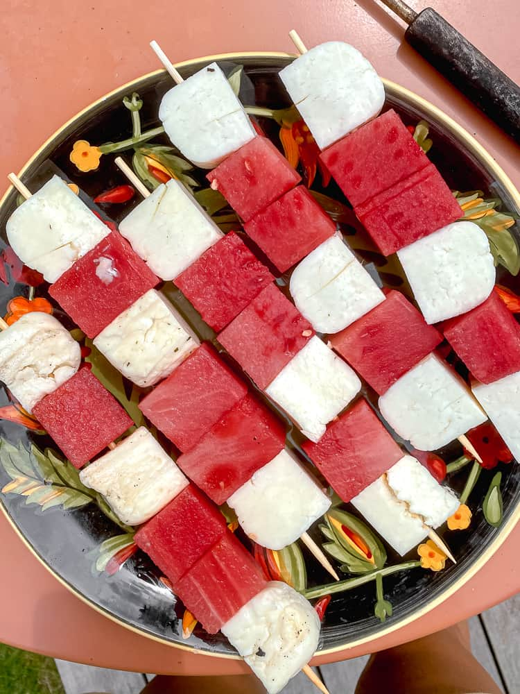 pre-grilled watermelon and haloumi cheese on skewers on a plate