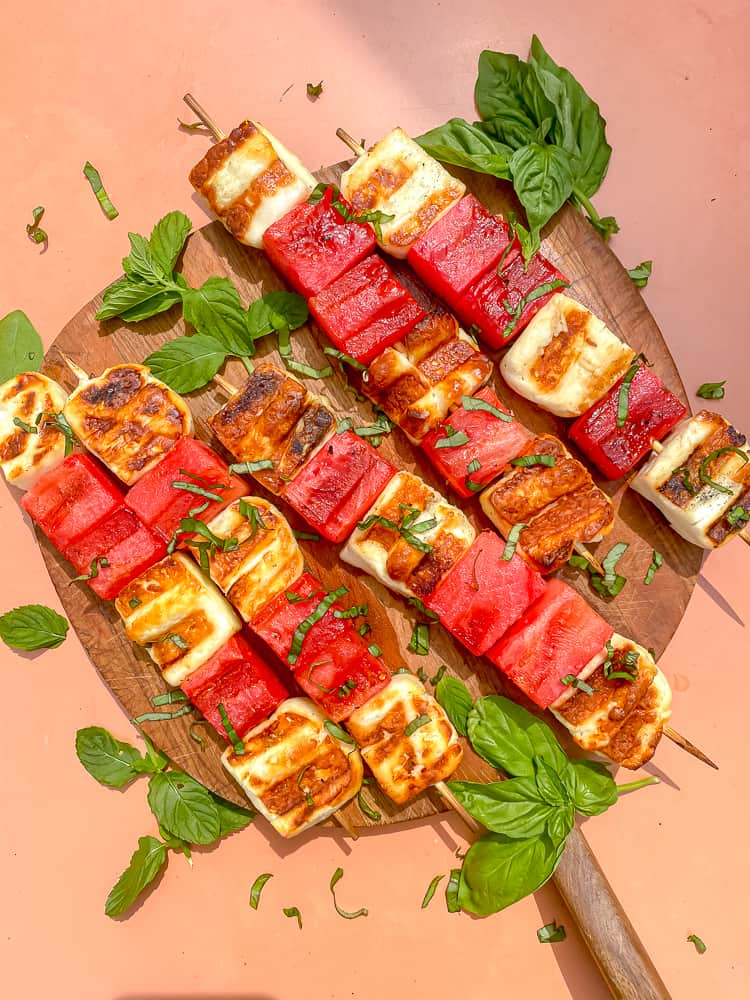 overhead photo of watermelon and halloumi cheese on skewers topped with fresh basil and mint leaves
