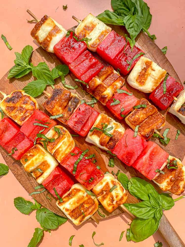 overhead photo of grilled watermelon and halloumi cheese on skewers topped with fresh herbs