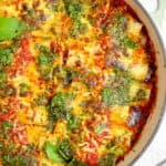white casserole pan with red sauce, pesto stuffed manicotti, browned bubbly cheese and pesto on top with fresh basil leaves