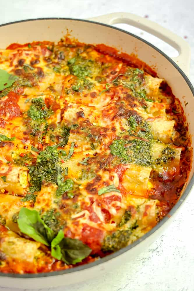 close up of cheesy pesto manicotti's in red sauce in a white casserole dish