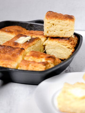 cast iron skillet with stacked up biscuits and a sliced open biscuit on plate