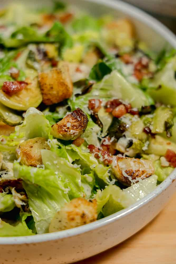 close up of roasted brussels sprout in a caesar salad