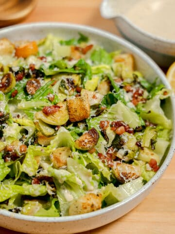 bowl with brussels sprouts, lettuce, pancetta, and croutons, with caesar dressing
