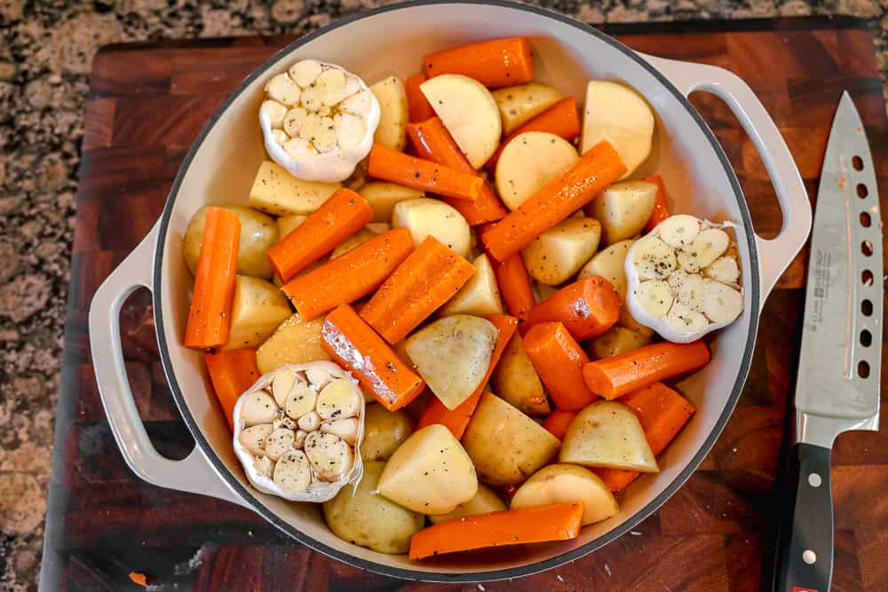 potatoes, carrots, and whole garlics in a roasting pan