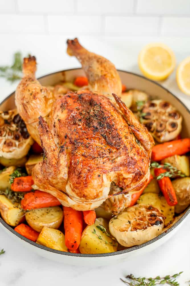 a whole roasted chicken sitting on bed of roasted potatoes and carrots