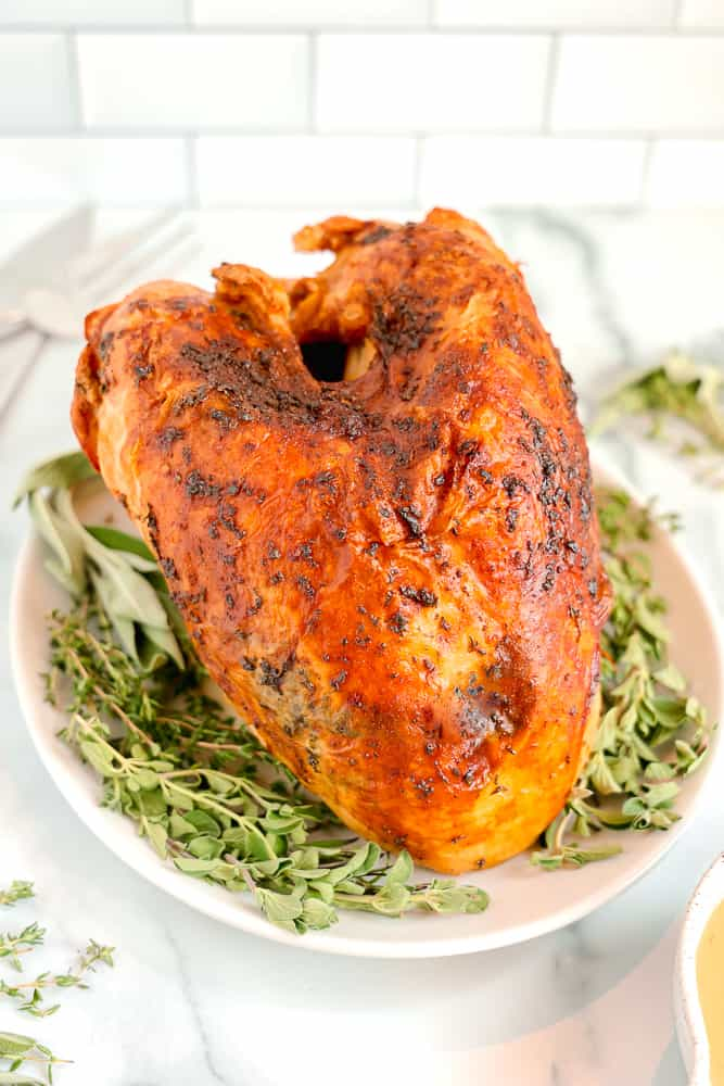 whole roasted golden turkey breast on bed of fresh herbs
