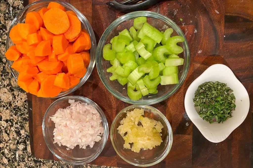 bowl of carrots, celery, garlic, shallot and herbs