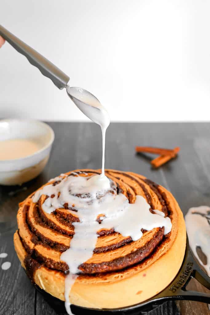 giant cinnamon roll with icing being poured on top