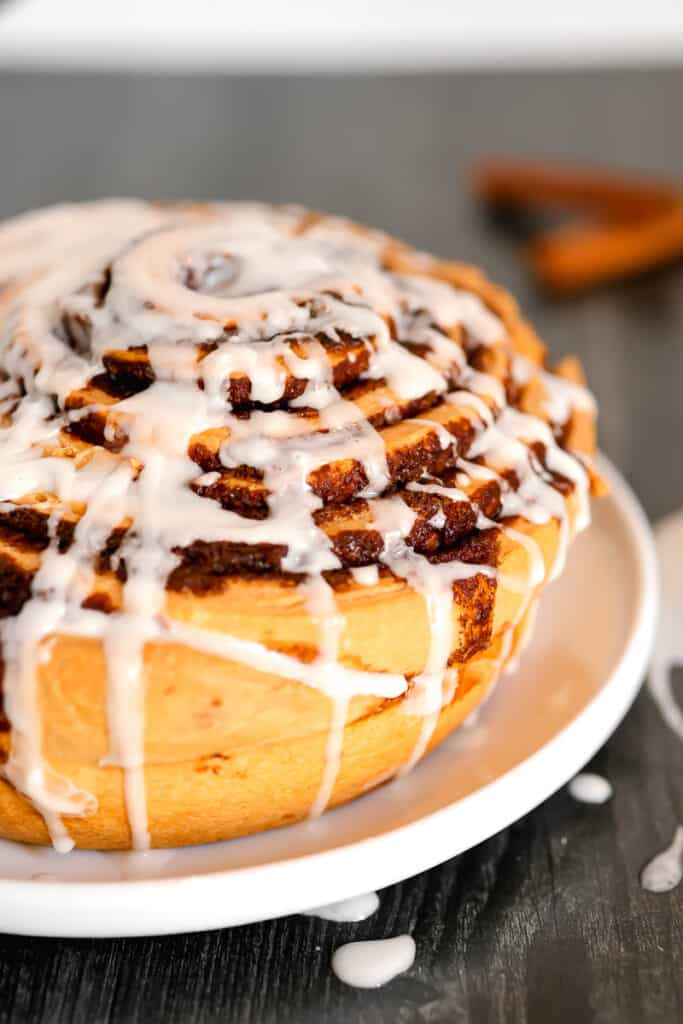 close up of giant cinnamon roll on a plate with frosting