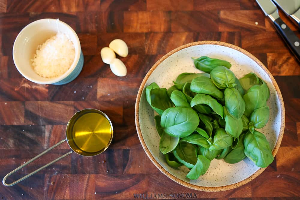basil leaves, olive oil, garlic, and parmesan on a cutting board