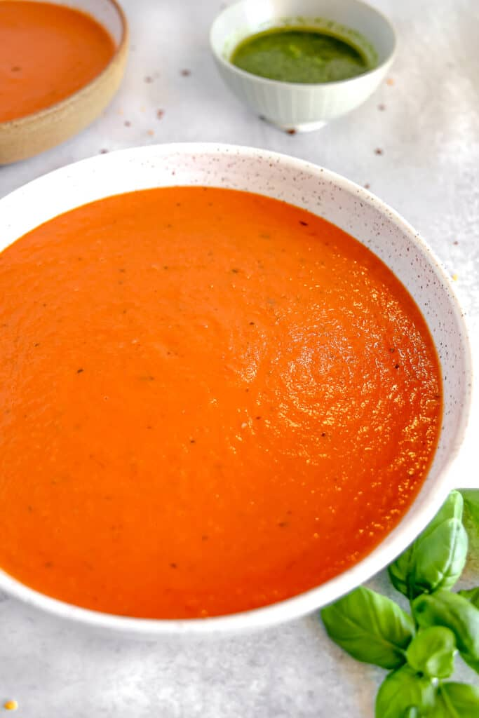 roasted red pepper tomato soup in a white bowl with fresh basil leaves