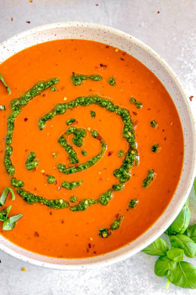 red pepper soup with a swirl of pistou and crushed red pepper flakes