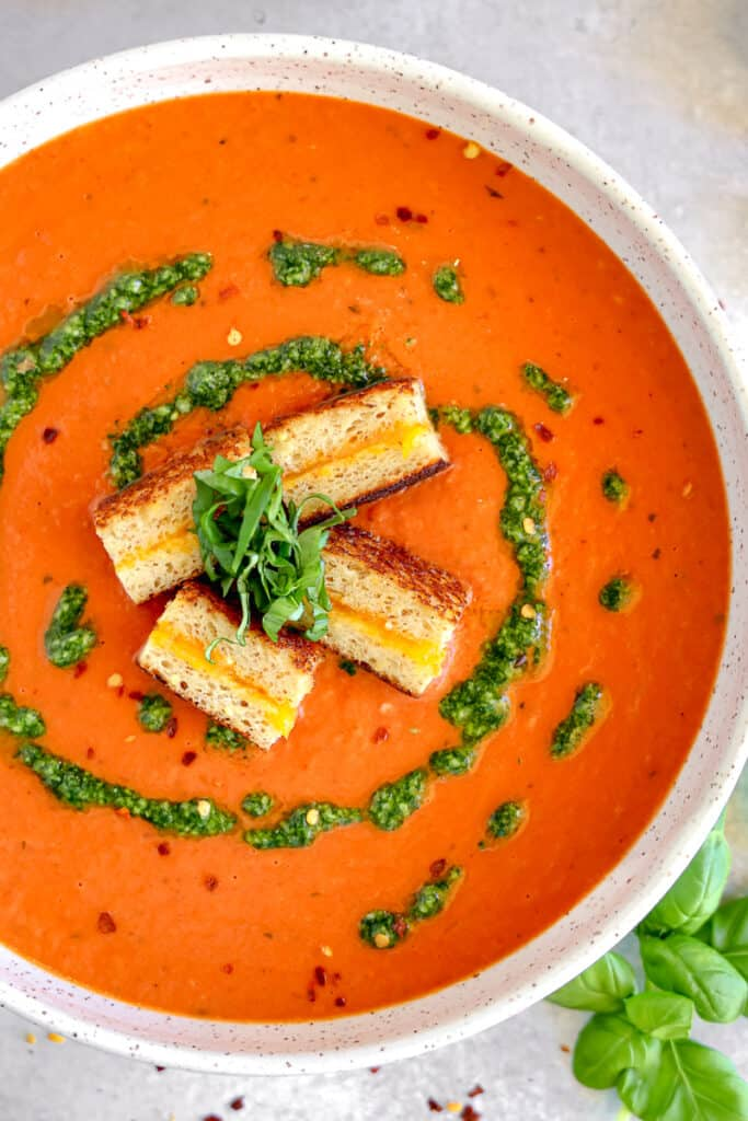 bowl of roasted red pepper tomato soup with grilled cheese croutons and basil swirl