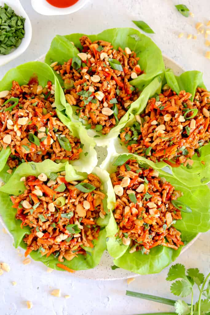 plate with lettuce cups fanned around stuffed with chicken carrots and more