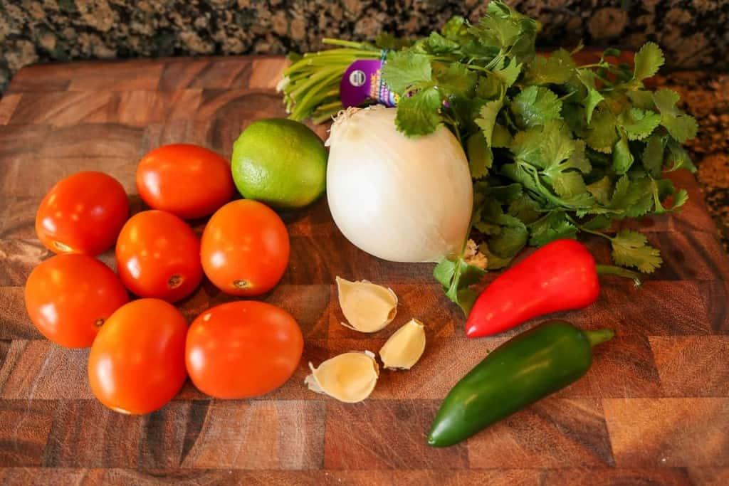 tomatoes, garlic, onion, cilantro on a cutting board