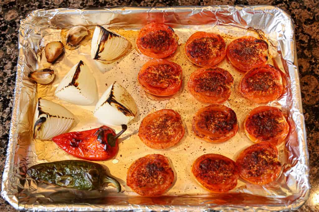 roasted tomatoes, onion, peppers, and garlic on a sheet pan