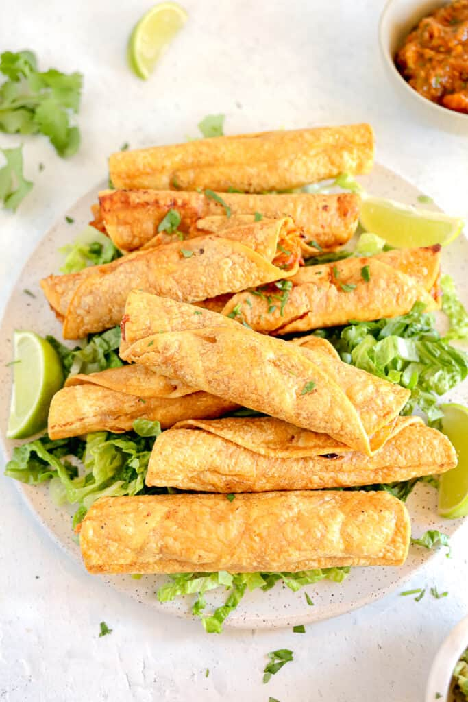 chicken taquitos piled onto a plate on a bed of lettuce