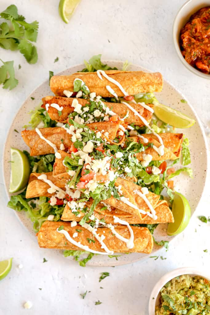 chicken taquitos on a plate topped with lettuce, tomatoes, crema, and salsa