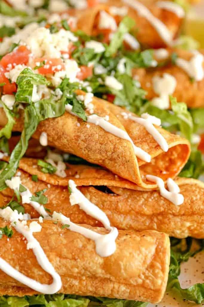 close up of chicken taquito with crema drizzle