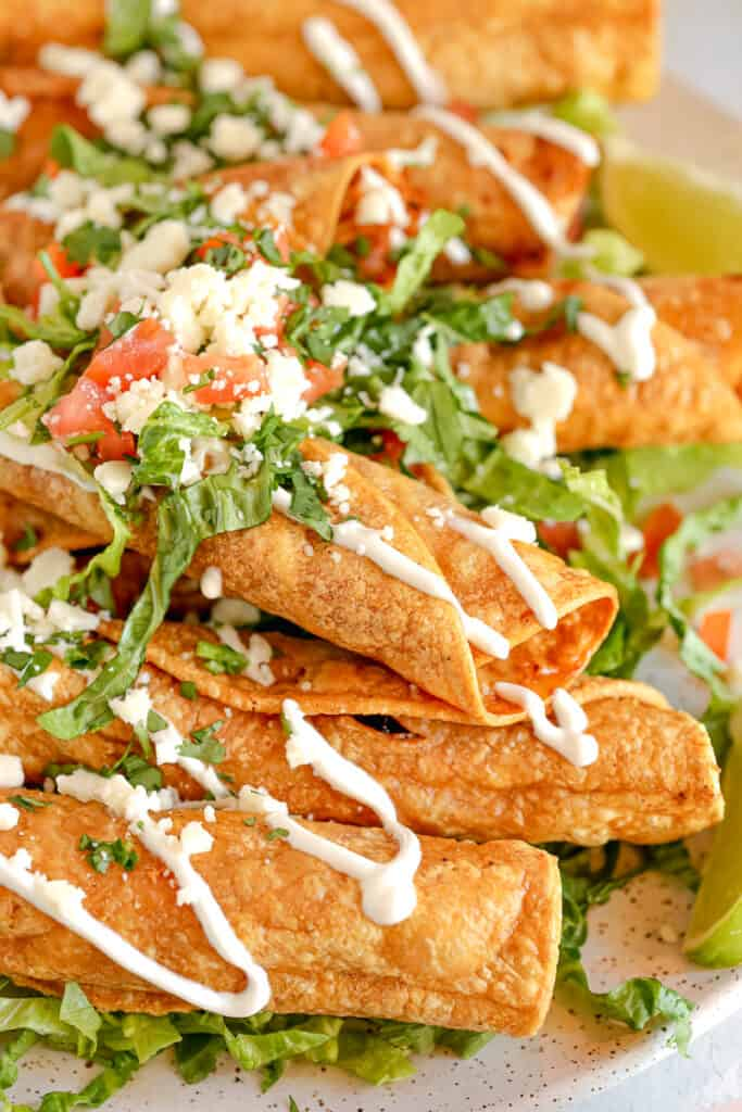 chicken taquitos topped with lettuce, cotija cheese, and crema drizzle