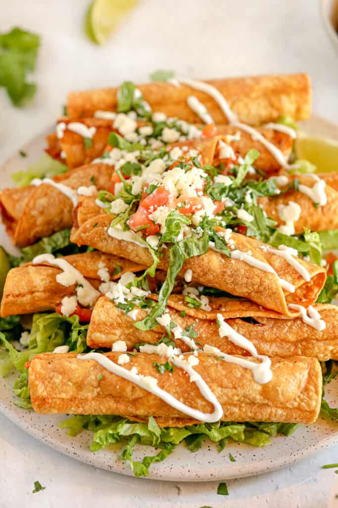 taquitos on a bed of lettuce topped with crema drizzle and tomatoes