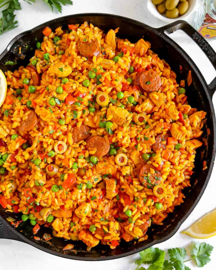paella rice, chicken, peas, and chorizo in a cast iron skillet