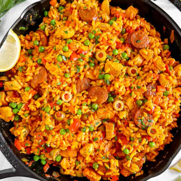 cast iron skillet with chicken and chorizo paella, peas, and herbs
