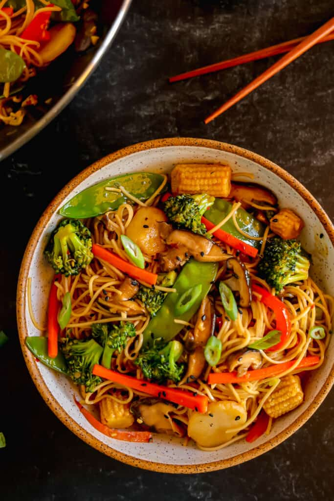lo mein noodles in a bowl with vegetables and chopsticks